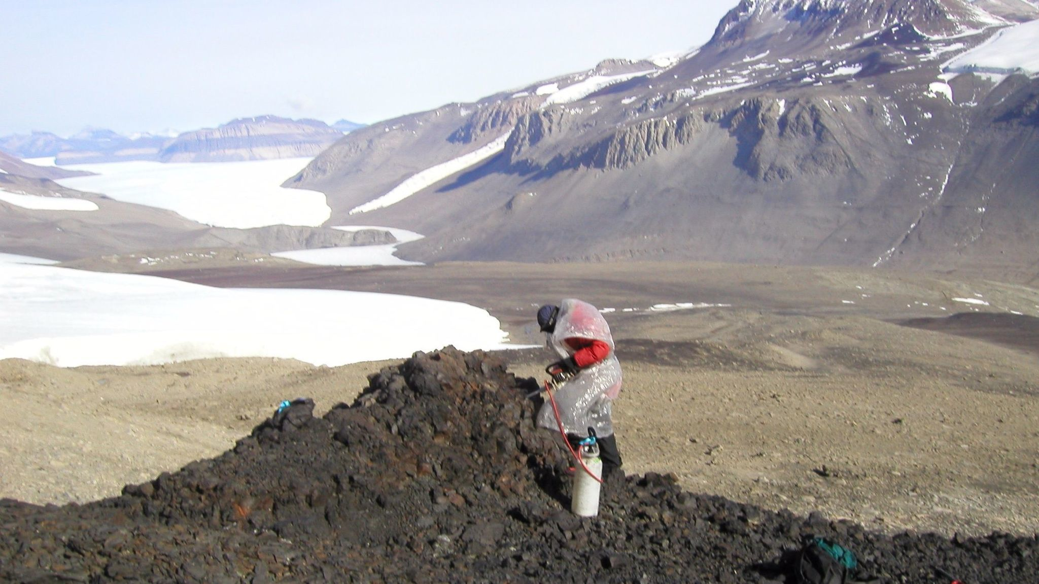 A scientist drills into a lava flow in Taylor Valley to study the ancient magnetic field.