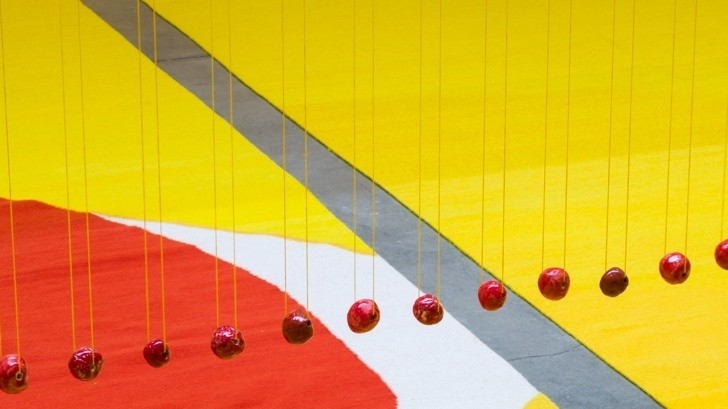 Glazed ceramic beads are suspended above woven rugs.
