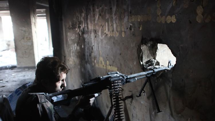 シリアの親政府軍のメンバーは、アレッポで見張りを介してピア。