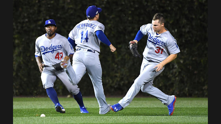 Dodgers teammates (from left) Howie Kendrick, Enrique Hernandez and Joc Pederson can't catch a pop fly in shallow left-center field by Cubs second baseman Javier Baez in the second inning of Game 1. To see more images, click on the photo. (Wally Skalij / Los Angeles Times)