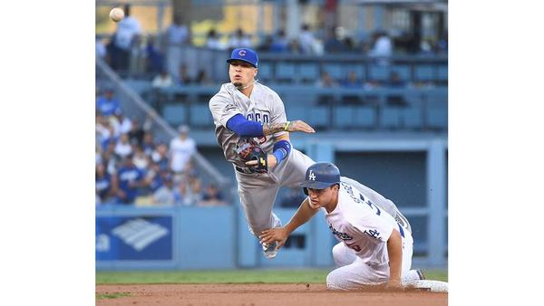 Cubs Javier Baez is forced into a throwing error while trying to complete a double play as Corey Seager slides into him. (Wally Skalij / Los Angeles Times)