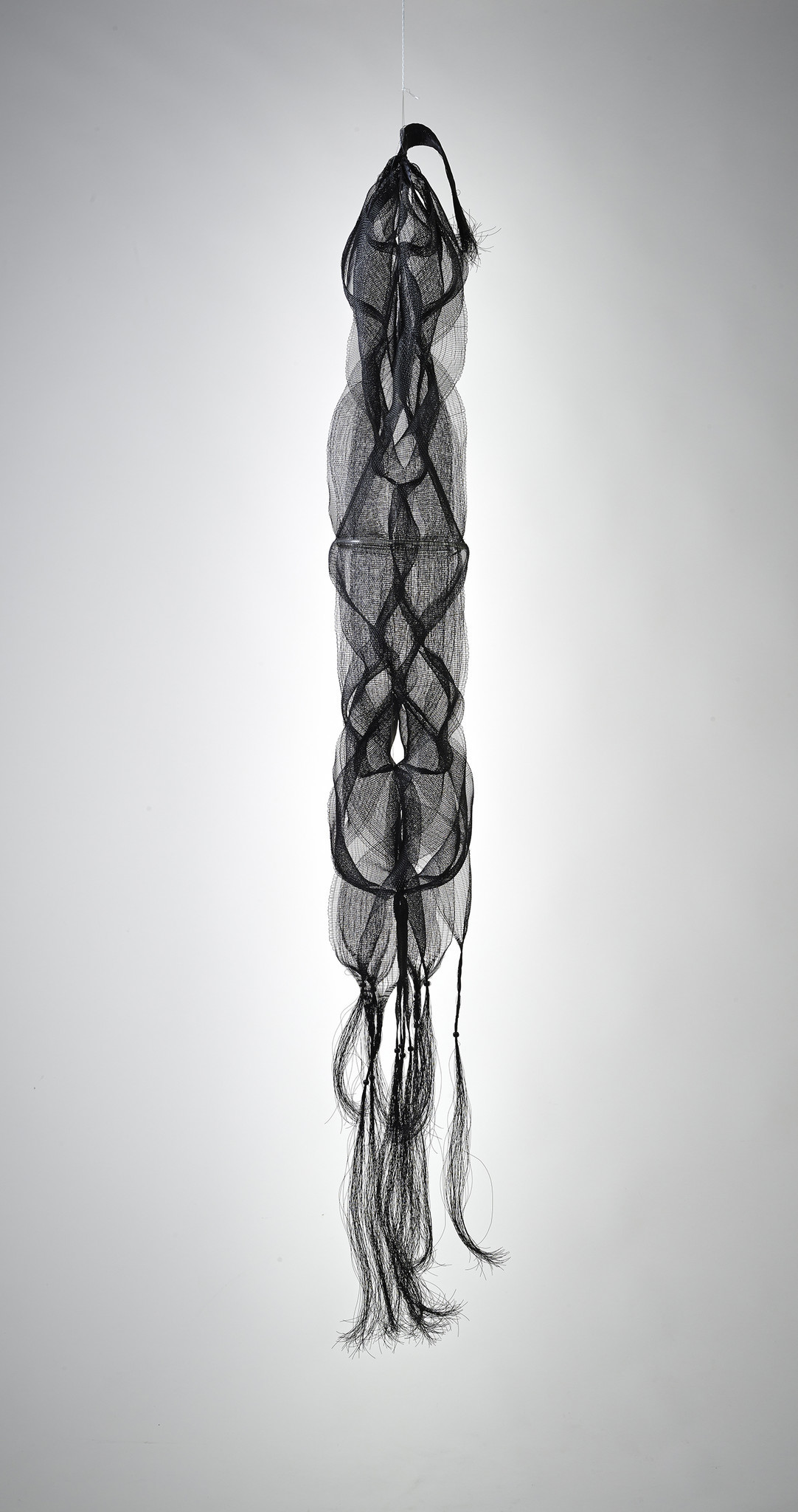 "Kay Sekimachi's ""Nagare I,"" 1967; black nylon monofilament, wood beads, plastic tubing; double, quadruple and tubular weave; 69 inches long, 13 inches diameter."
