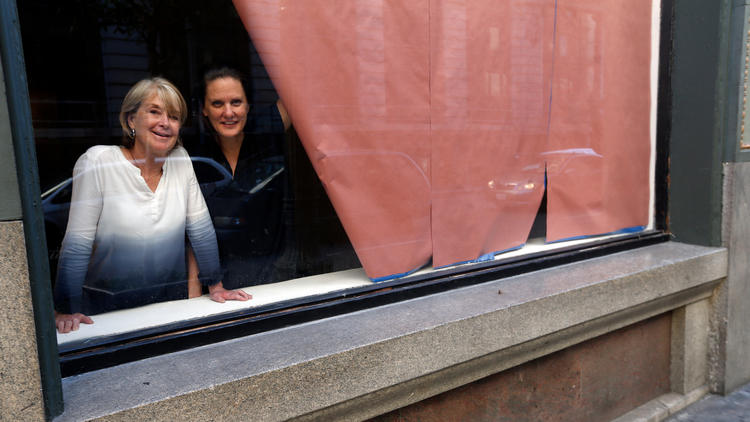 Artists Suzanne Lacy (left) and Andrea Bowers in the windows of the Main Museum in downtown L.A.