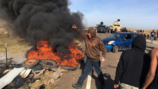 Demonstrators stand next to burning tires as armed soldiers and law enforcement officers assemble nearby.