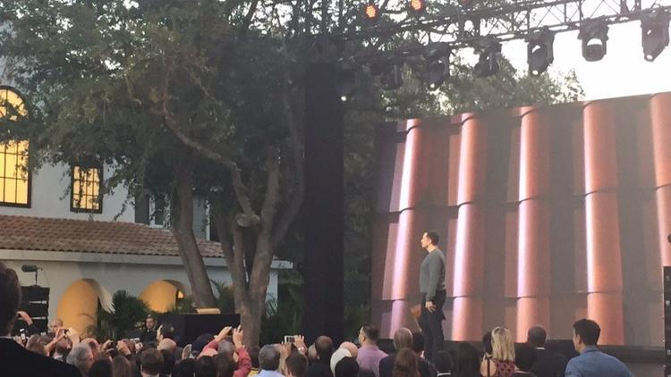 Elon Musk speaking in front of a crowd