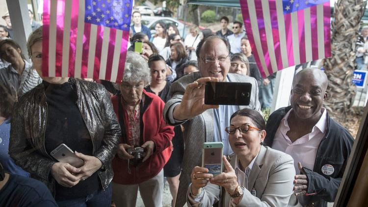 An overflow crowd watches through a window during a rally with Kamala Harris at the Democratic Party's headquarters in Santa Clarita. (Brian van der Brug / Los Angeles Times)