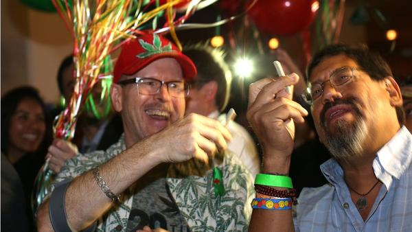William Britt, of Long Beach, and Al Moreno, of Fullerton, both proponents of Proposition 64, the California Adult Use of Marijuana Act, celebrate a win at the DoubleTree hotel. (Rick Loomis / Los Angeles Times)
