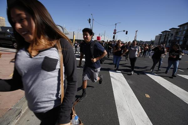Students run across the intersection at 1st and Alameda streets during an anti-Trump walkout on Monday. (Brian van der Brug / Los Angeles Times)