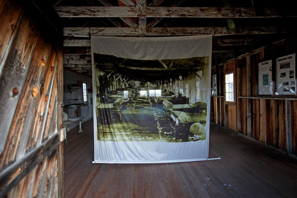 A banner hung in place in a barracks at Camp Tulelake depicts what it looked like when it housed Japanese American internees during World War II. (Gary Coronado / Los Angeles Times)