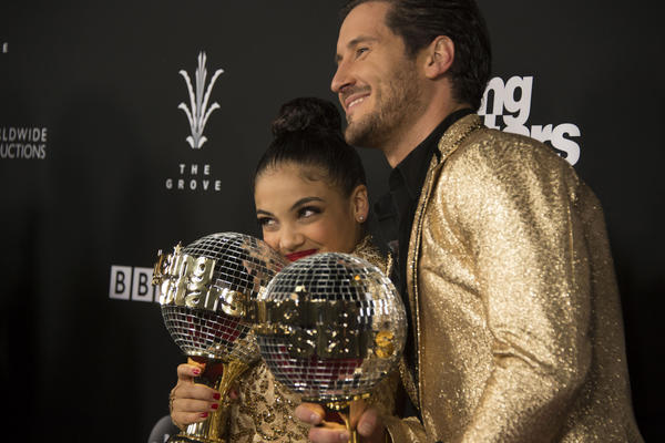 """Laurie Hernandez and Valentin Chmerkovskiy hold the Mirrorball Trophy after winning the 23rd season of """"Dancing With the Stars."""" (Eric McCandless / ABC)"""