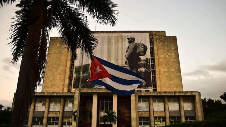 The Cuban flag hangs at half-staff in front of a picture of Fidel Castro on the facade of the Cuban national library in Havana. (Ronaldo Schemidt / AFP/Getty Images)