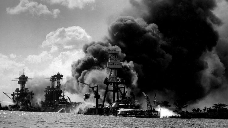Smoke billows from the USS Arizona (right) on the morning of Dec. 7, 1941. On the far left, the USS West Virginia begins to sink following the Japanese attack on Battleship Row. The ship in between, the USS Tennessee, suffered only minor damage.