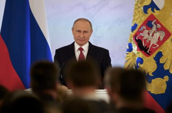 Russian President Vladimir Putin smiles as he gives his annual state of the nation address in the Kremlin in Moscow on Thursday. (Pavel Golovkin / Associated Press)