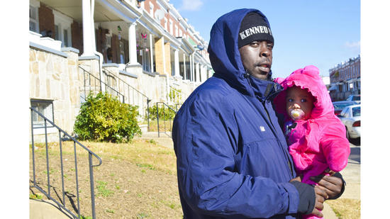 Rafiq Shaw stands outside his home with his daughter.