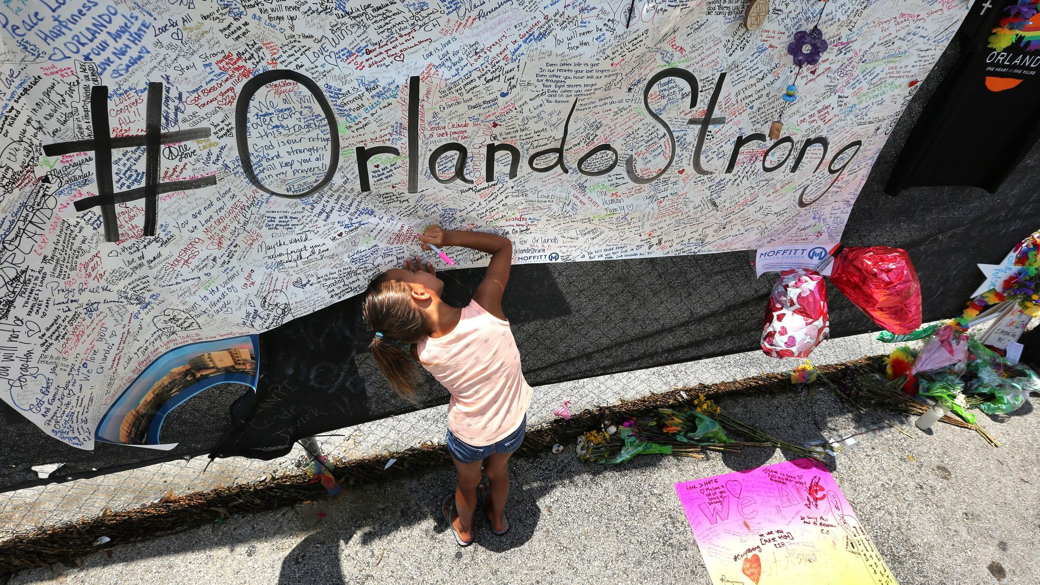 Kyndall Whitley, 7, signs a poster at the roadside memorial at Pulse nightclub.