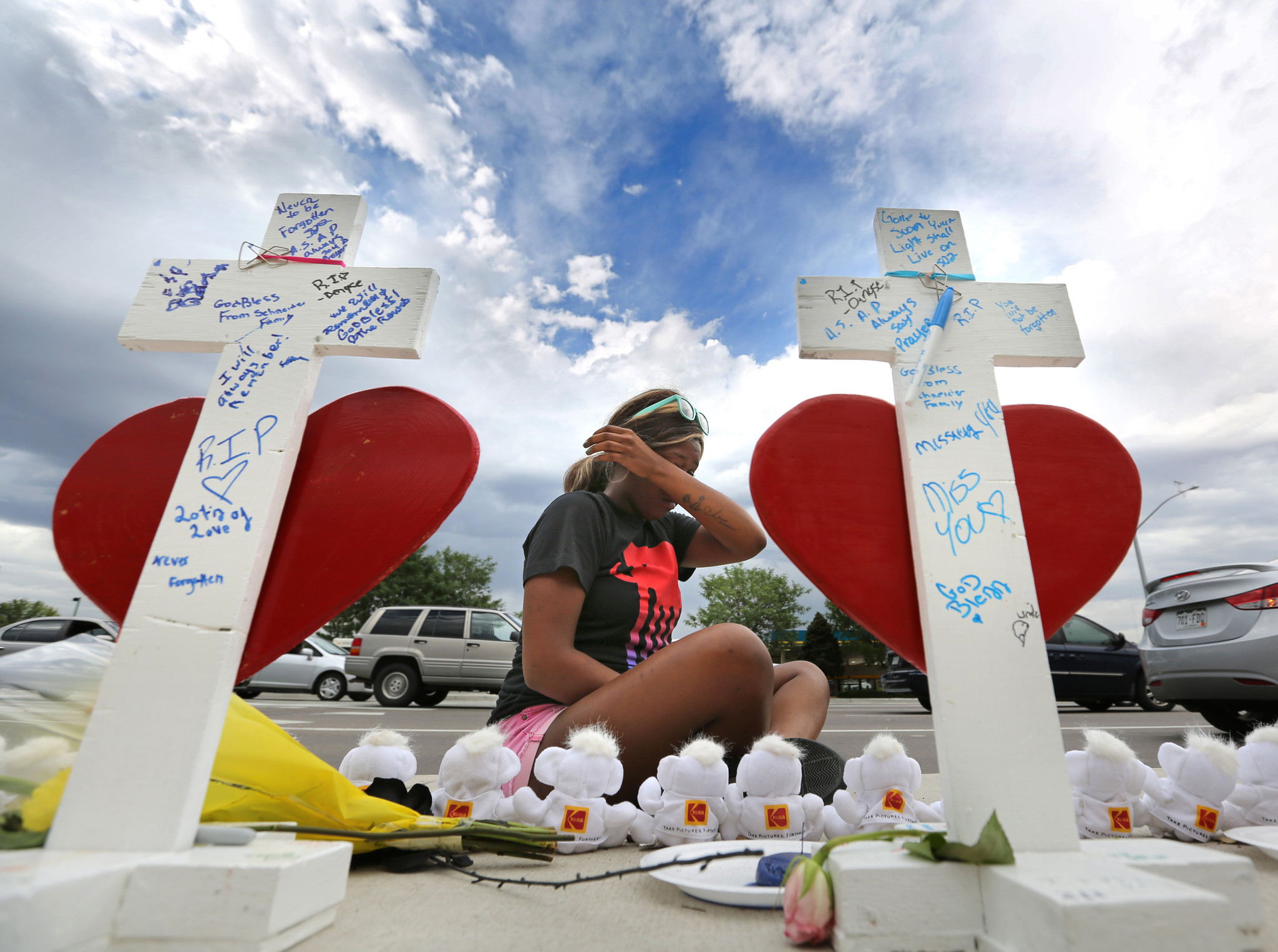 Margaret Lavin — 23, whose cousin was killed in the movie theater shooting in Aurora, Colo. — cries at a makeshift memorial of crosses marking the massacre's fourth anniversary.