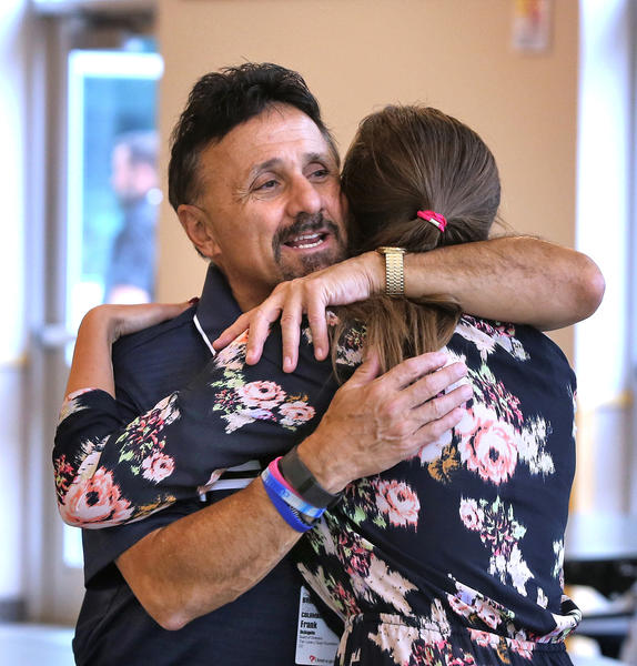 During a visit to Columbine High School, Kristina Anderson, who survived the 2007 Virginia Tech shooting, hugs Frank DeAngelis, the school's former principal.
