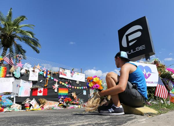 A friend of two Pulse victims places flowers at a memorial outside the club.
