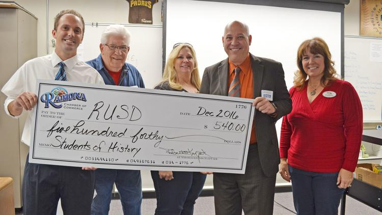 "Ramona High history teacher Doug Banwart accepts a $540 Ramona Chamber of Commerce educational grant for his ""Students of History"" project."