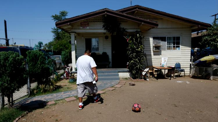 Jose Gomez, at his home on South Hicks Avenue in East Los Angeles, is among thousands whose yards have been tested for contamination from the former Exide plant. (Gary Coronado / Los Angeles Times)