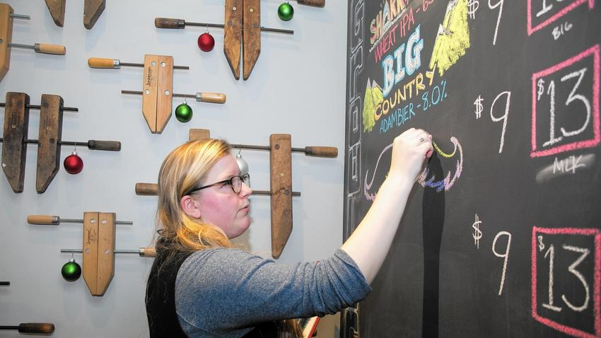 Gabby Golub of Chicago does chalkboard art for bars and restaurants in addition to driving for Lyft and working part time at her old high school. (Kristan Lieb / Chicago Tribune)
