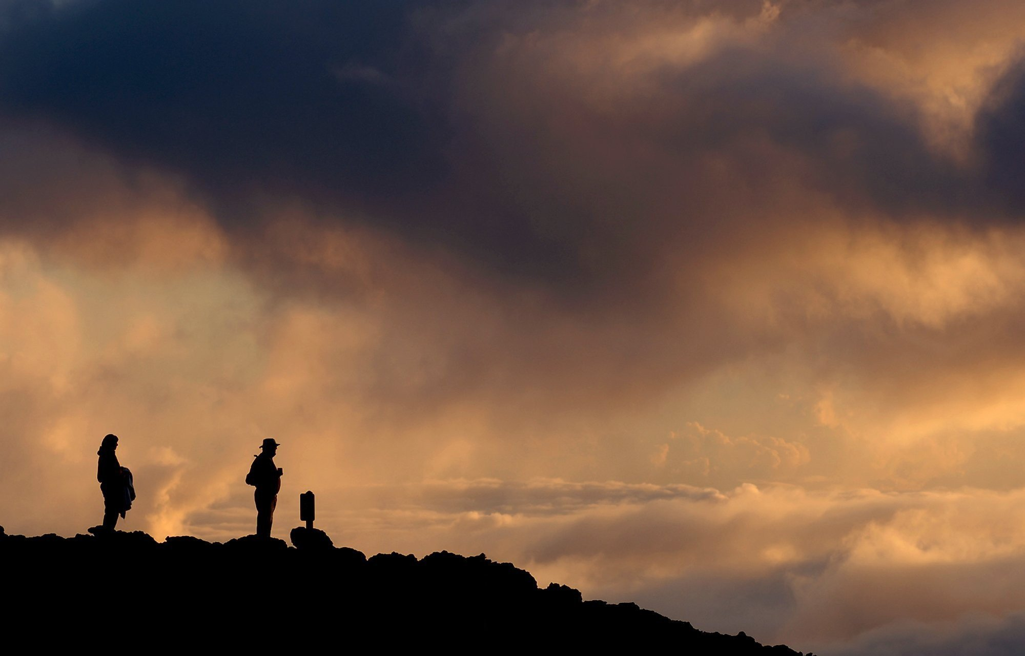 Visitors watch the sunrise atop Haleakala, a volcano rising 10,023 feet in Haleakala National Park on Maui.