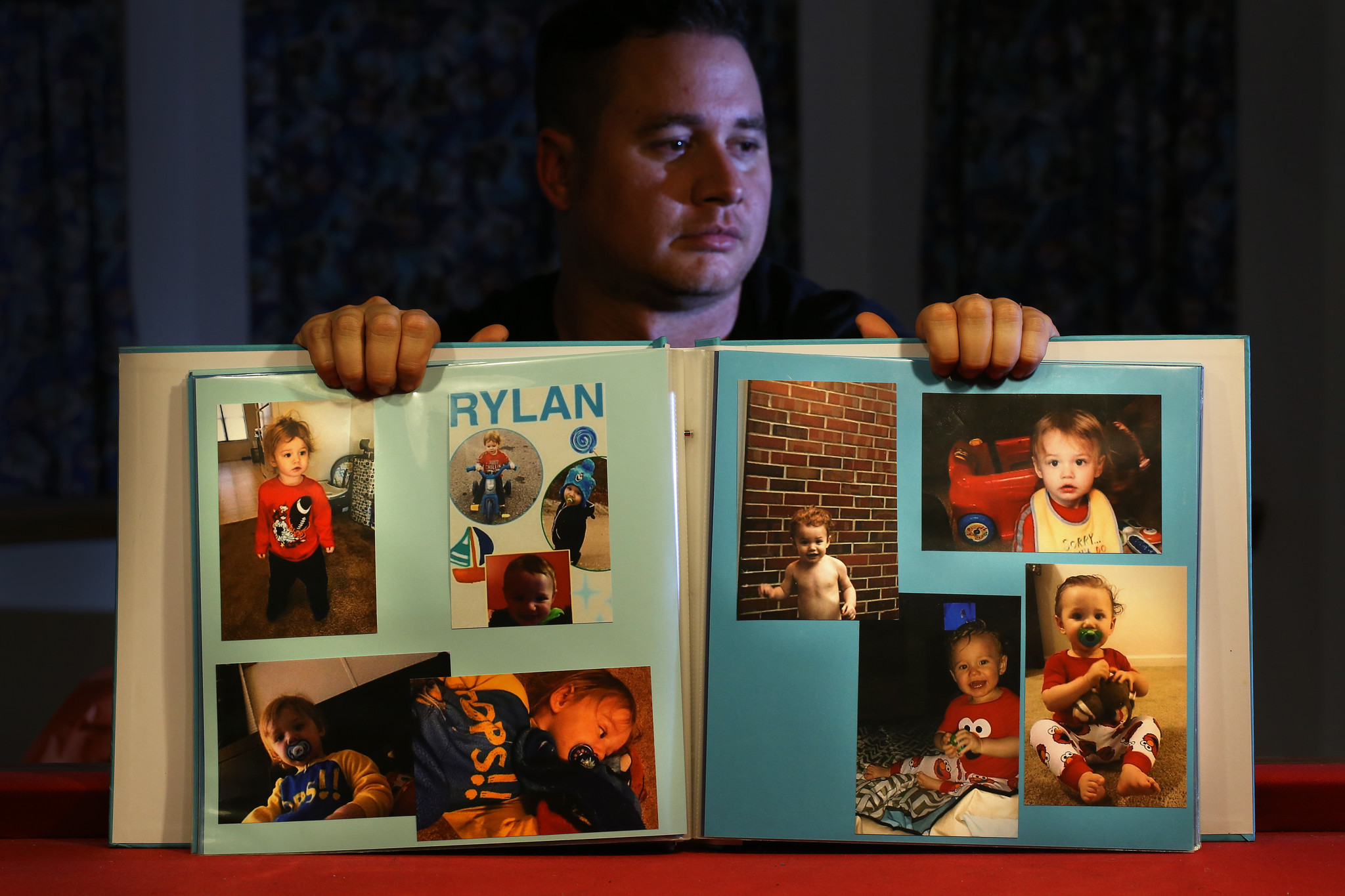 Corey Ott displays a book of photographs of his son, Rylan Ott, who apparently drowned in a North Carolina pond while under the care of his mother, Samantha Bryant.