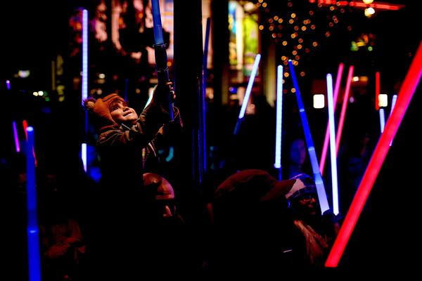 "Jay Cotton Jr., 4, of Whittier, sits on his father Jay Cotton's shoulders during a lightsaber vigil for ""Star Wars"" actress Carrie Fisher held in Downtown Disney. (Rick Loomis / Los Angeles Times)"