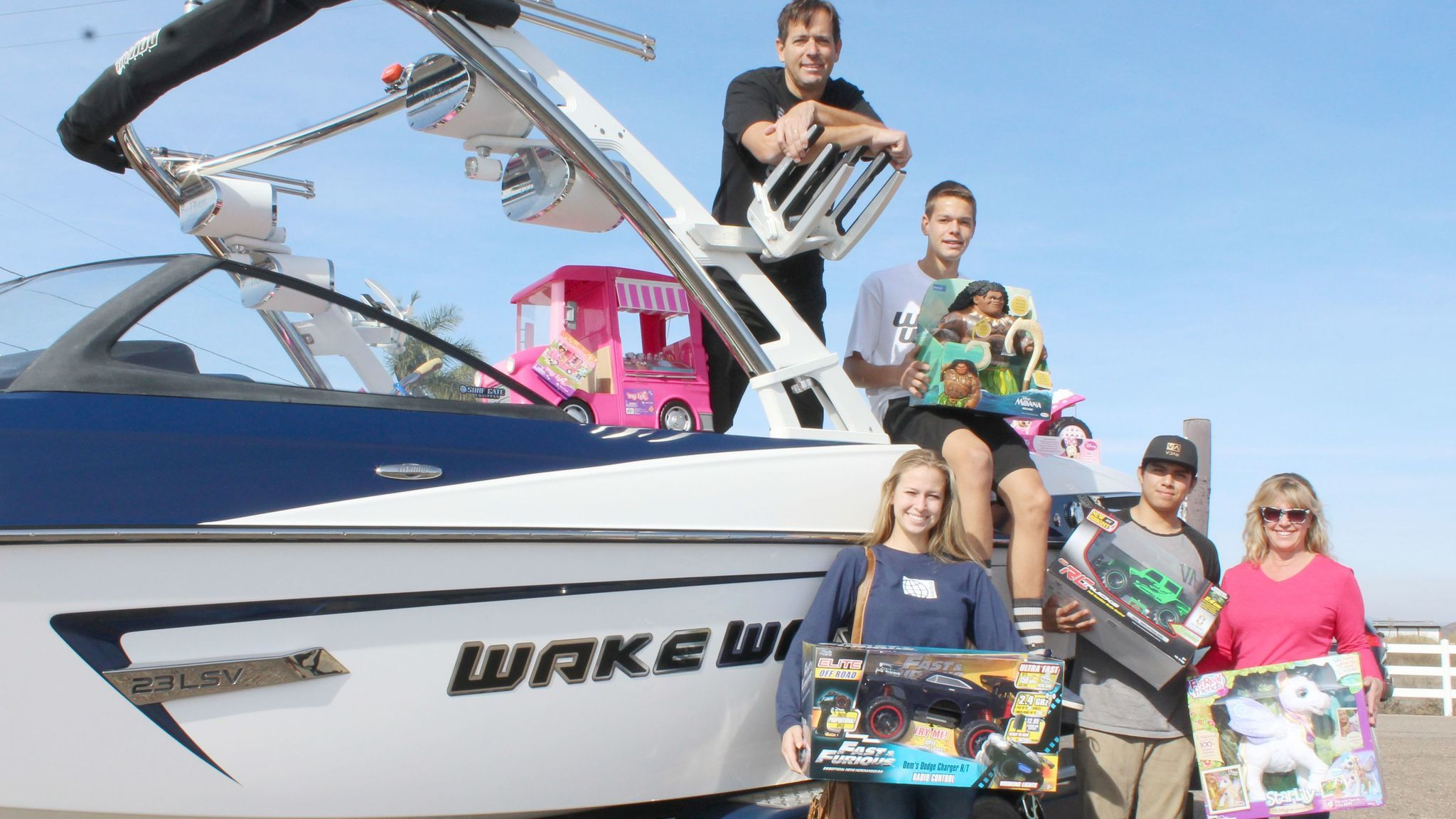 Tammy and David Williams with children Blake, 16, and Paige, 18, and friend Mario Castro, show some of the toys that arrived by boat.