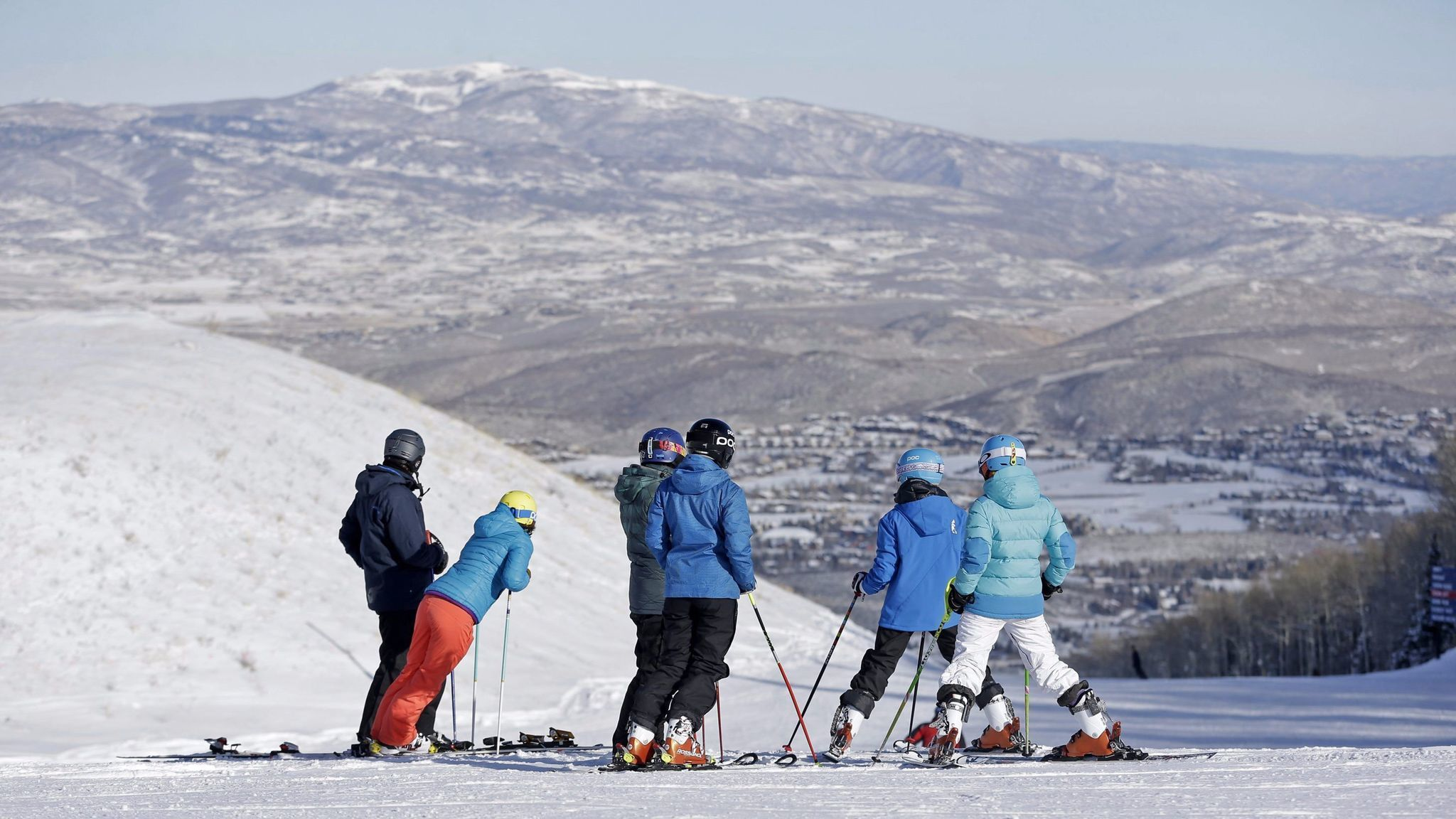 Skiers at Park City Mountain Resort stand on top of a hill in Park City, Utah.