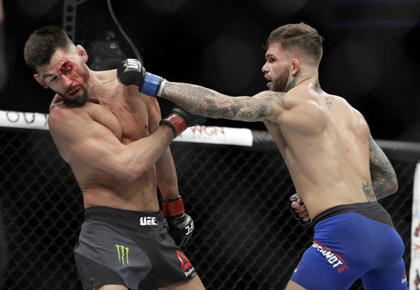 Cody Garbrandt strikes a bloodied Dominick Cruz during their bantamweight championship fight at UFC 207. (John Locher / Assocaited Press)