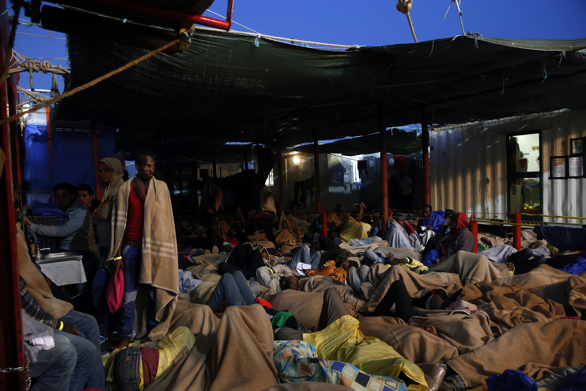 Migrants sleep on the deck of the rescue ship Vos Hestia, operated by Save the Children, as it heads for Sicily. The migrants, of several nationalities, were bound for Europe.