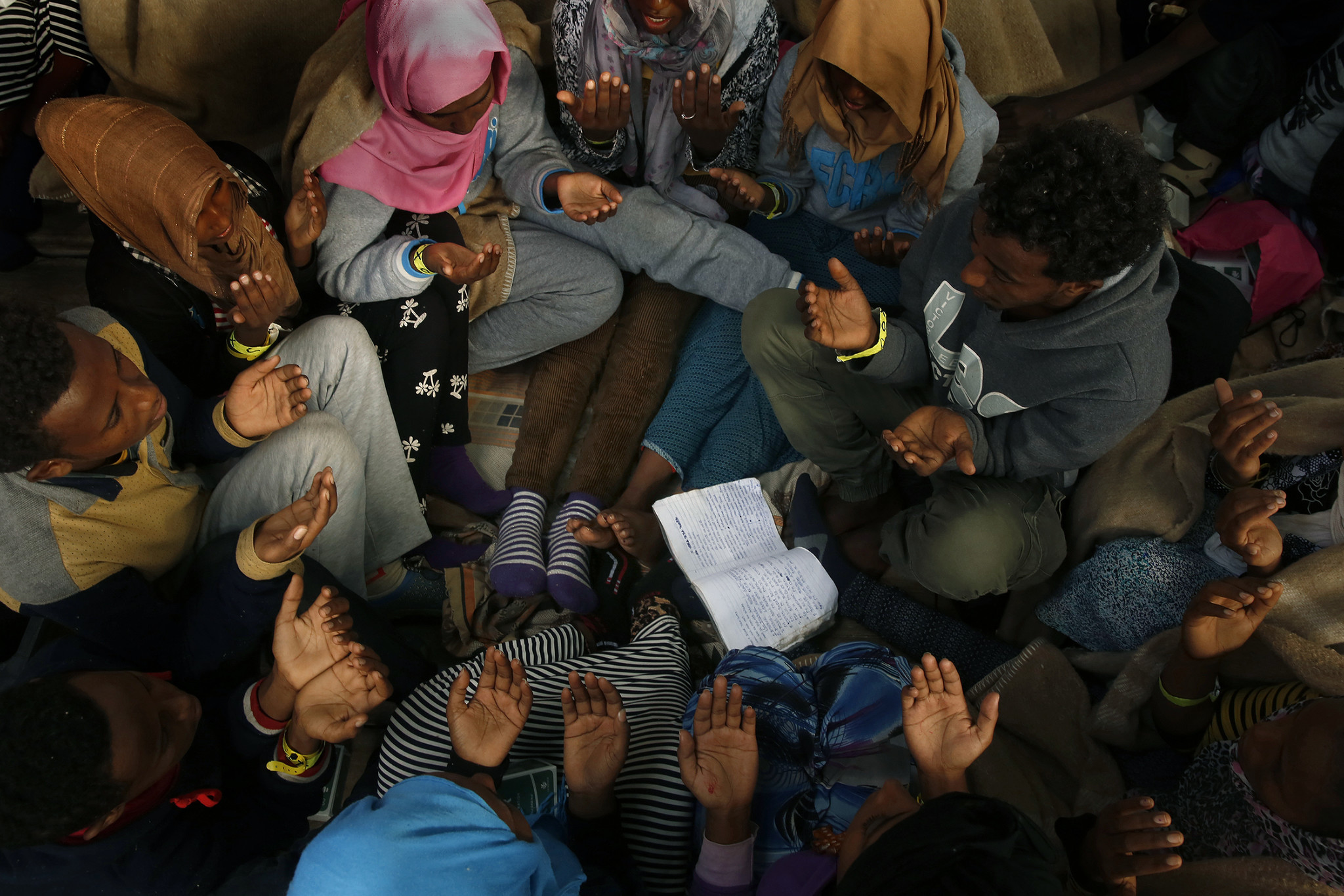 Migrants gather in a circle to sing and pray during the journey to Sicily. About 300 of the 412 rescued migrants were from Eritrea, where Christians and Muslims make up the majority of the population.