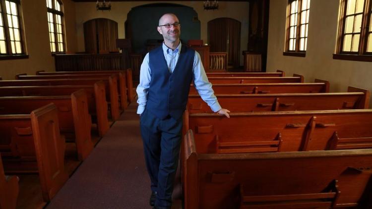 Jeff Zlotnik, berdiri di dalam Gereja Swedenborgian yang kosong di University Heights, tempat baru bagi komunitsa Vihara Dharma Bum.