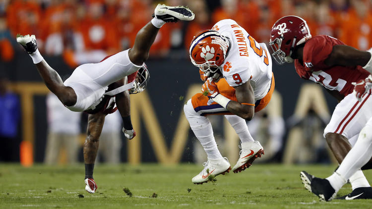 Clemson running back Wayne Gallman (9) is brought down by Alabama defensive back Tony Brown (left). To see more images from the game, click on the photo above. (John Bazemore / Associated Press)