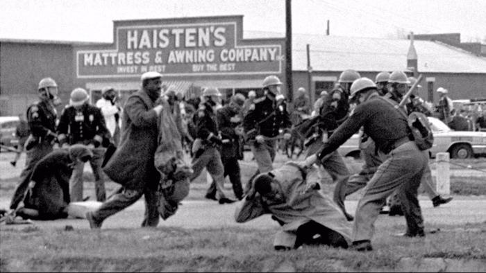 A young John Lewis is seen in the foreground being clubbed by a state trooper during a civil rights protest in Selma, Ala., in 1965. (Associated Press)