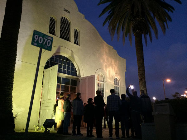 Members of the Actors' Gang theater in Culver City gather before their space on the eve of the presidential inauguration to turn on a light as a symbol of tolerance. (Carolina A. Miranda / Los Angeles Times)