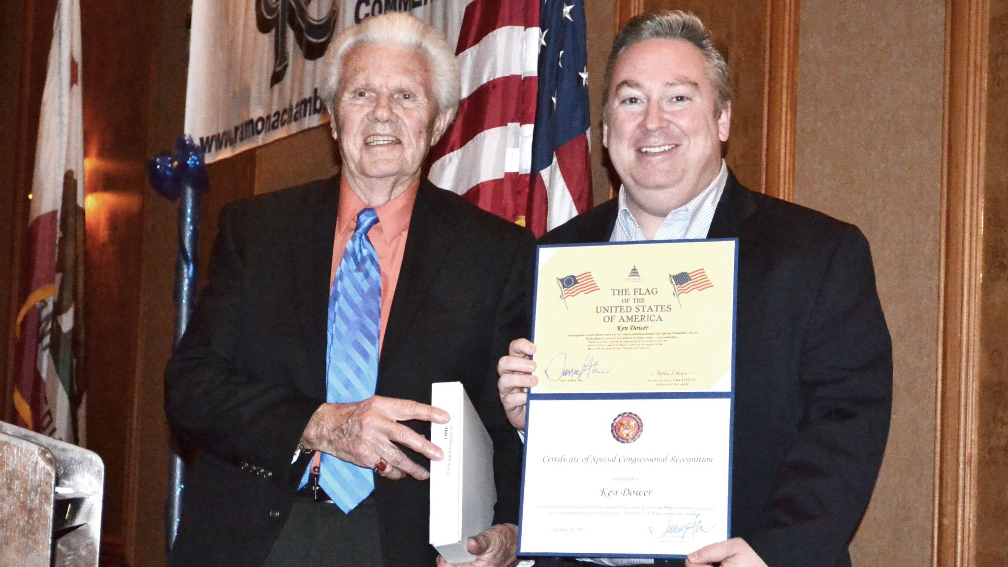 Ken Dower, Lifetime Achievement award recipient, accepts an American flag that flew over the U.S. Capitol from Michael Harrison, chief of staff for Congressman Duncan Hunter. Dower, a Navy and Marine Corps veteran, retired with 35 years in military intelligence.