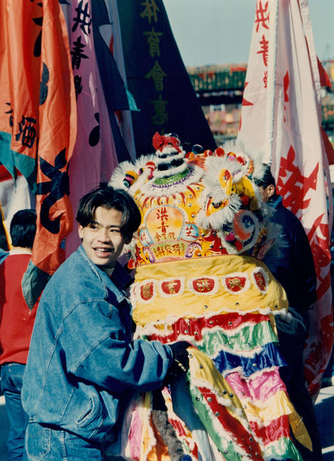 A young man pops out from under a 20-foot-long dragon to take in the Chinese New Year celebration in Chinatown in1988.