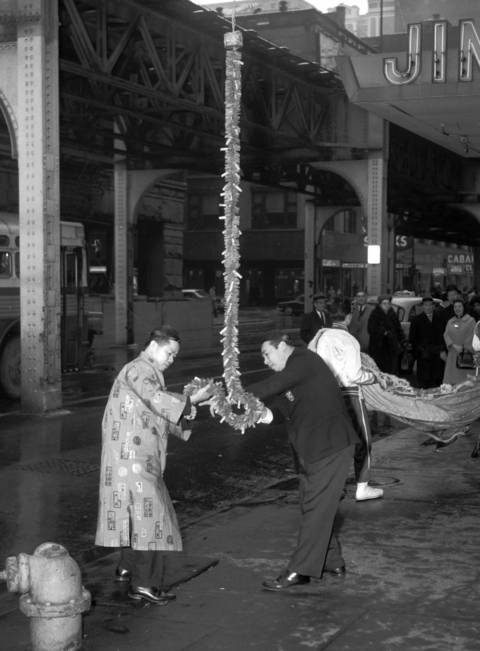 Two men light a string of firecrackers for a Chinese New Year celebration outside Jimmy Wong's restaurant at 426 Wabash St. in February 1964.