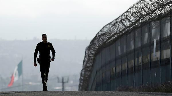 FILE - In this June 22, 2016, file photo, Border Patrol agent Eduardo Olmos walks near the secondary fence separating Tijuana, Mexico, background, and San Diego in San Diego.