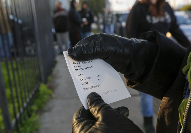 A worker shows a ticket with her assignment for the day.