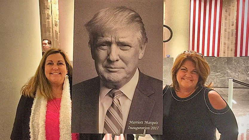 Stephanie Norvell and Chris Anderson stand on either side of a poster of President Donald Trump.