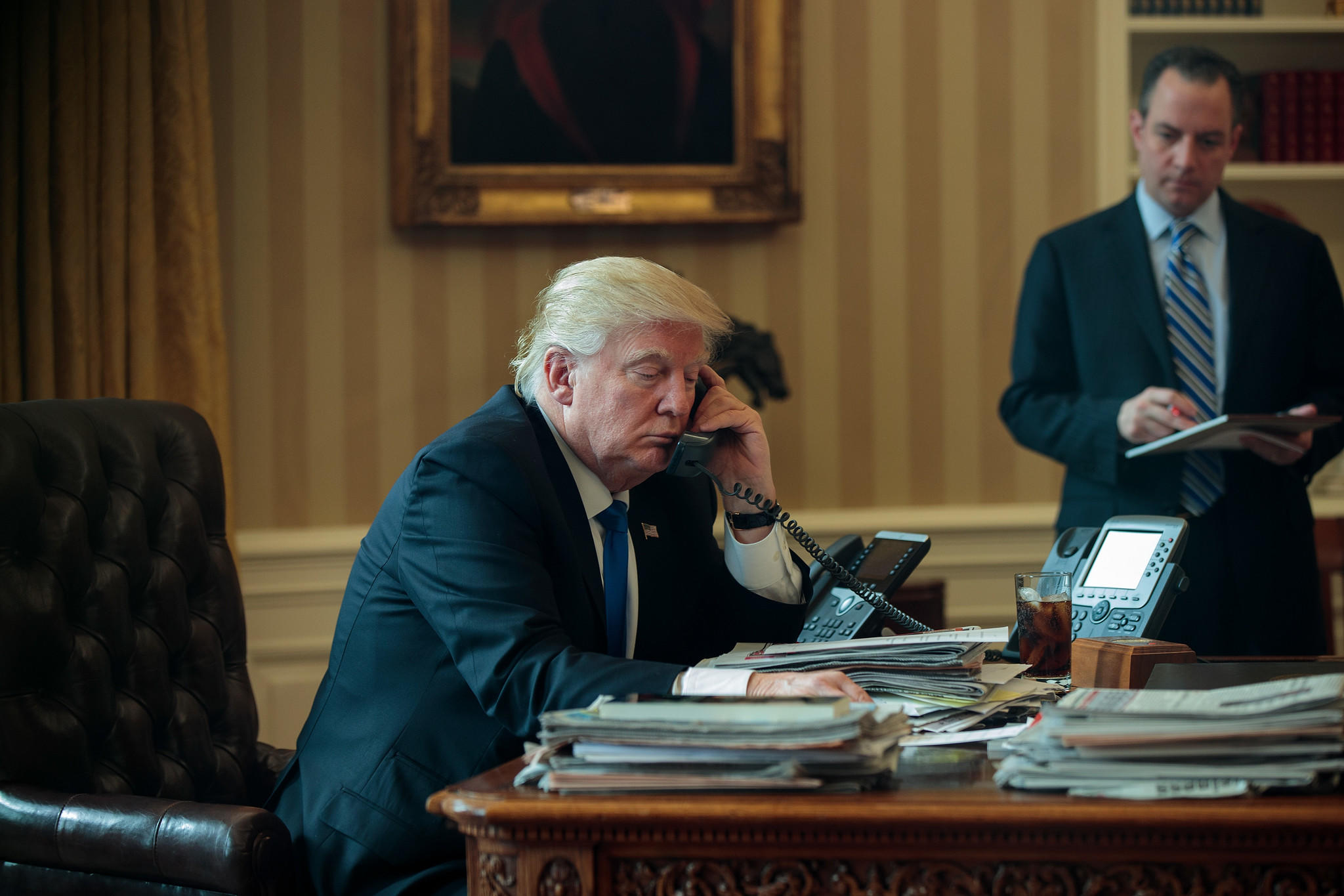 Trump speaks by phone with Putin as White House Chief of Staff Reince Priebus looks on.