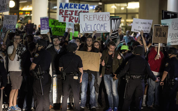 Protesters are held back by airport police on Sunday at LAX. (Brian van der Brug / Los Angeles Times)