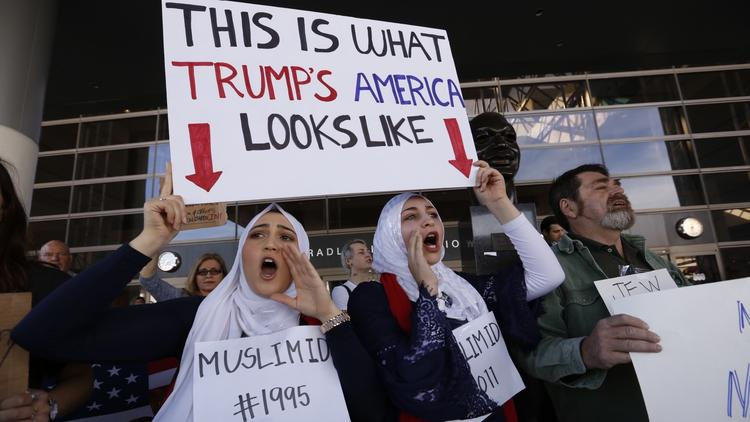 Noor Hindi, left, and Shah Najjar, middle, join the protest at the Tom Bradley International Terminal at Los Angeles International Airport on Monday. (Al Seib/Los Angeles Times)