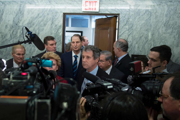 Senate Democrats speak with reporters after boycotting Finance Committee confirmation votes. (JIM WATSON / AFP/Getty Images)