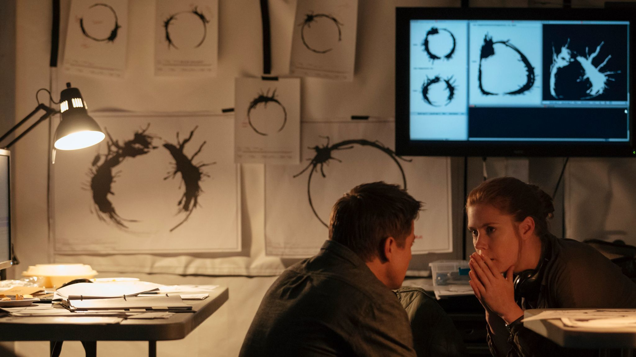"Jeremy Renner (as Ian Donnelly) and Amy Adams (linguist Louise Banks) sit before alien logograms in ""Arrival."""