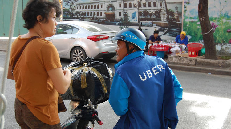 Bike-sharing apps like uberMOTO are replacing street-corner men who for decades offered cheap motorcycle trips. (L.R. Meyers)