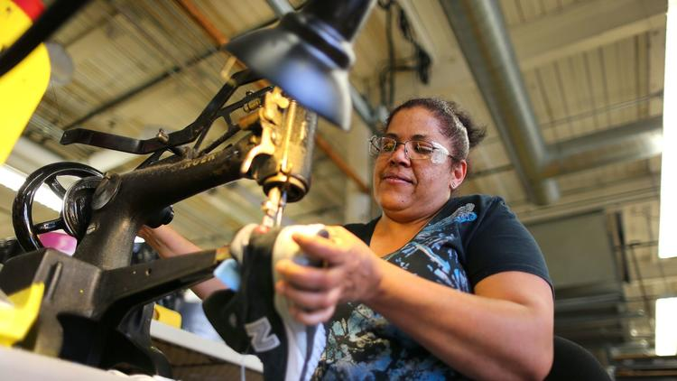 Eddy Maria Taveras uses a Singer sewing machine to repair a running shoe at the New Balance factory in Lawrence, Mass. (John Tlumacki/ Boston Globe / Getty Images)